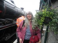 Sonia Cameron pictured alongside some of her hanging baskets at Mallaig station [see news item].<br><br>[John Yellowlees&nbsp;/07/2012]