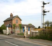 Looking north over the level crossing at Hessay on the Harrogate - York line in April 2009, with the closed (1958) station beyond. Accommodation for the current crossing keeper/signalman is the annexe on the left of what is now a private residence. The lever frame and instruments are located on the platform below the arc lamp. <br><br>[John Furnevel&nbsp;24/04/2009]