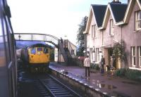 Trains crossing at Strathcarron station following a shower of rain in the summer of 1974. Approaching the camera is a Class 26 hauled service from Kyle of Lochalsh bound for Inverness.<br><br>[David Spaven&nbsp;//1974]