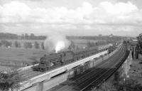 A Black 5 takes a train north over the River Eden at Etterby, thought to be in the summer of 1967. In the right background a diesel shunter is approaching with a short freight on the goods lines and is just about to pass the sidings of Willowholme power station. <br> <br><br>[Robin Barbour Collection (Courtesy Bruce McCartney)&nbsp;//1967]