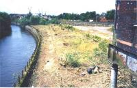 Scene looking west from Benalder Street bridge over the site of Partick Central alongside the River Kelvin in July 2001. For some reason most of the trees and shrubbery had been cleared from the site around this period, thus allowing the old station platforms to be seen for the first time in many years. The station building stands on the right [see image 24316].<br><br>[Colin Miller&nbsp;/07/2001]