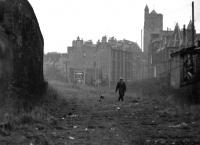 One man and his dog approaching along the Caledonian trackbed from the direction of Merchiston station in 1972. View is south west, with Dundee Street footbridge [see image 29621] a short distance behind the camera. On the right is Angle Park Terrace with the tower of St Michael's Church, standing in the background at no 1 Slateford Road. [Editor's note: A definite 'Kitchen Sink' feel about this one - listen for the church bells tolling, a Salvation Army band playing and the sounds of a Mr Burton murdering his trumpet in one of the top floor tenement flats in the background. Only problem is it's not raining....]<br><br>[Bill Jamieson&nbsp;//1972]
