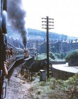 Photograph taken from a carriage window showing Ivatt 2-6-2T no 41241 running parallel with Low Mill Lane as it takes a KWVR service away from Keighley station in the late sixties. The train is just about to cross the River Worth bridge on the curving gradient. <br><br>[Robin Barbour Collection (Courtesy Bruce McCartney)&nbsp;//]