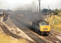A 'Western' diesel hydraulic lays a smokescreen over Stoke Gifford Yard in the northern suburbs of Bristol as it passes with a South Wales - Paddington express in the summer of 1971. Stoke Gifford is now home to the successful Bristol Parkway station. The locomotive cannot be identified from the photograph but has been suggested as being no 1027 <I>Western Lancer</I>. [with thanks to Dave Blake].<br> <br><br>[Bill Jamieson&nbsp;24/07/1971]