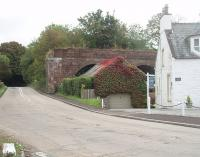 Part of the surviving remnants of Tongland Viaduct are seen here behind a house alongside the A711 road. The road crosses the River Dee running parralel to the old Kirkcudbright railway but then swings sharp right to pass under the line although the road bridge has been removed since the line closed in 1965. <br><br>[Mark Bartlett&nbsp;19/09/2010]