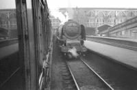 Photograph taken from the window of a train arriving from the north in bay platform 8 at Carlisle station. Stanier Pacific no 46221 <I>Queen Elizabeth</I> is standing at plaform 7. The date is thought to be around 1957, prior to the removal of the station's (by then less than attractive) end screens and the cutting back of the overall roof. <br><br>[Robin Barbour Collection (Courtesy Bruce McCartney)&nbsp;//1957]