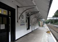 A look south along the Platform 1 at Dunkeld on 20 September.� The line is bidirectional and the platform is used by all services except one each weekday.� The station may look like it is staffed, but in fact is hasn't been manned for some years though this building is occupied.� Notice that some of the canopy brackets seem to have had their ornate mouldings knocked out and replaced with something more utilitarian.� Note also the wooden steps on platforms which are below standard height.� The sign on the door reads <I>Private offices leased from British Rail.� It is regretted that there are no facilities for the travelling public</I>.� <br> <br> <br><br>[David Panton&nbsp;30/09/2010]