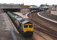 <I>Fastline</I> liveried 66434 heading south through Perth station on 11 October 2010 with the return Lairg oil tanks. A DMU stands at the Dundee platform in the background while repair and refurbishment work continues on platform 4.<br><br>[Brian Forbes&nbsp;11/10/2010]