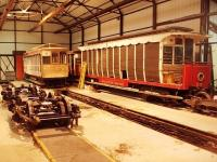 Every passenger carrying vehicle on the Manx Electric Railway is over 100 years old. This picture, taken in the workshop building, gives an illustration of some of the ongoing work required to maintain such an old fleet. The bogies in the foreground have just been fitted with refurbished traction motors and will now be refitted to a tramcar who's bodywork has been restored in the main running shed.  Alongside is a trailer car that has had a large amount of woodwork renewed. Car 29, a <I>toastrack</I> with ratchet brakes only, is stored unserviceable and is a long term restoration candidate. Note the unlined inspection pit. Picture taken with kind permission of MER engineering staff.<br><br>[Mark Bartlett&nbsp;08/10/2010]
