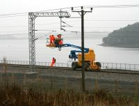 A grey day just west of Forrestfield on 12 October sees a 3-man team engaged in electrification work in connection with the Airdrie - Bathgate project. Hillend reservoir forms the backdrop with Caldercruix in the left background. <br><br>[John Furnevel&nbsp;12/10/2010]