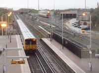 A 6-car EMU leaves Kirkdale and heads for Liverpool passing the EMU depot, although this being the <I>rush hour</I> there is only one train in the sidings. Picture taken from the modern street level bridge that also carries the ticket office.<br><br>[Mark Bartlett&nbsp;21/10/2010]