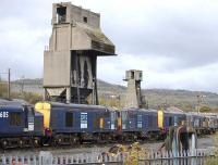 Part of a row of three class 37s and six class 20s, stored for DRS at Carnforth MPD on 21 October, with the old coal and ash towers dominating the scene.<br> <br><br>[Bill Roberton&nbsp;21/10/2010]