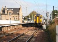 Having picked up passengers at Kirknewton station on 12 October, the driver of unit 156437 has left his cab to depress the plunger which will activate the level crossing barriers over the B7031 just behind the camera. The train is the 13.26 Edinburgh Waverley - Glasgow Central.<br><br>[John Furnevel&nbsp;12/10/2010]