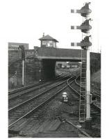 Looking south from the up platform at Newton-on-Ayr station in 1985, showing the massive signalbox which, for many years, towered above Prestwick road together with a fine collection of semaphore signals, alas all now gone! Ayr MPD stands in the background with a selection of diesel locomotives sharing the accommodation with DMU stock. <br> <br><br>[Ken Browne&nbsp;//1985]