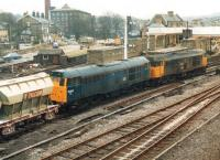 31319 leads 31202 eastbound through Skipton station in March 1988 with a loaded Tilcon working from Swinden Quarry. 08707 stands in the siding in the centre background.<br><br>[David Pesterfield&nbsp;22/03/1988]