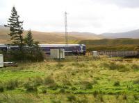 The 11.01 Inverness - Kyle of Lochalsh train pulls away from Achnasheen station under threatening clouds on 1 October 2009 and heads west onto the bridge across the River Bran.<br><br>[John Furnevel&nbsp;/10/2009]