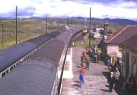 Rail-borne guests of BR from Inverness have just alighted from a southbound train at Dalwhinnie in 1976 to view the reinstatement of double track to Blair Athol. A northbound passenger service is in the Down loop, while an engineer's train waits in the refuge sidings.<br><br>[Frank Spaven Collection (Courtesy David Spaven)&nbsp;//1976]