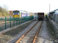 The 14.00 <I>Northern</I> DMU from Saltburn to Bishop Auckland slows for the Shildon stop on 23 November 2010. On this side of the fence is the NRM site with the north wall of the main exhibition hall to the right. The view is east from the end of the 'excursion platform' located within the site and shows one of the coal wagons for which Shildon works became famous during its later years (over 10,000 HAA wagons were built there - almost the whole fleet).<br><br>[John Furnevel&nbsp;23/11/2010]