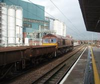 With the giant Unilever works complex forming a backdrop, 66207 gets a load of open wagons and container flats on the move through Bank Quay station. The train has just left Arpley Yard at the south end of the station and is heading north towards Winwick Junction. <br><br>[Mark Bartlett&nbsp;04/11/2010]