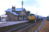 Bunting in evidence as a Class 24-hauled train for Inverness calls at Alness on the first day of service following the station's re-opening in May 1973. Sadly, the attractive Highland Railway station building has since been demolished.<br><br>[David Spaven&nbsp;07/05/1973]