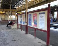 This poster board and bench on the central platforms at Gilmour Street look is if they are of the same, considerable vintage and it's pleasing that they have been allowed to survive.� What posters that board must have seen.� What... um... people the bench must have seen. The windows in the background always intrigue me: sash windows in what is essentially the open air.� I am reminded of whoever it was who took a car door as his luxury on Desert Island Discs so that if it got too hot he could wind the window down.� Photographed on 27 November 2010.<br> <br><br>[David Panton&nbsp;27/11/2010]