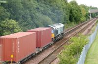 DRS 66410 takes the 12.56 Elderslie - Grangemouth containers north east towards Cumbernauld on 26 July 2006 having just passed the platforms of Greenfaulds station. <br><br>[John Furnevel&nbsp;26/07/2006]