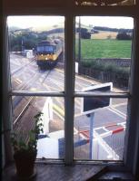 View from Insch signal box as an Inverness - Aberdeen train runs over the level crossing into the station in August 1987.<br><br>[Ian Dinmore&nbsp;/08/1987]