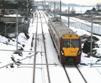 The 12.40 Helensburgh Central - Edinburgh Waverley runs east past the former Forrestfield station on 14 December 2010. Hillend reservoir can be seen in the right background with the town of Caldercruix beyond. <br><br>[John Furnevel&nbsp;14/12/2010]