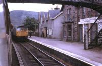 Kyle line trains, hauled by BRCW Type 2 Class 26 locos, cross at Achnasheen in the summer of 1972. View from the Kyle bound train as the driver of the Inverness working hands over the single line token.<br><br>[David Hindle&nbsp;//1972]