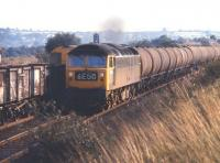 Class 47 no 1879 on a northbound train of oil tanks, thought to be returning empty to Tees-side, on the Midland 'Old Road' at Killamarsh in July 1971. The train is passing a pair of class 20s heading an unbraked train of 16t coal wagons south on the up line.<br><br>[Bill Jamieson 21/07/1971]