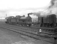The north end of Inverurie station on 26 March 1959 sees J36 0-6-0 no 65303 engaged in manoeuvres in conjunction with Barclay no D2414 prior to taking out a freight.  The Barclay (diesel mechanical)   shunter, which entered service early in 1959, has no coupling rods and looks to be in course of delivery.<br><br>[Robin Barbour Collection (Courtesy Bruce McCartney)&nbsp;26/03/1959]