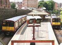 A Cathcart Circle train (L) passes a Neilston line service at Queens Park station in July 2005. View west from the Victoria Road entrance. <br><br>[John Furnevel&nbsp;03/07/2005]