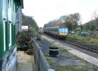 A Redmire - Leeming DMU passing the former Wensley station on 3 November 2004. The old station has been converted to a holiday cottage, but with the original railway theme retained. To the left beyond the bay window, now the master bedroom, was the private waiting room once used by  local landowner Lord Bolton. The Wensleydale Railway continues to work on restoration of the full 22 mile route from the ECML at Northallerton to the S&C at Garsdale.<br><br>[John Furnevel&nbsp;03/11/2004]