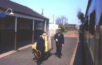 Classic BR uniforms glimpsed at Ellon from the 12.25 Aberdeen-Fraserburgh train on Saturday 1st May 1965, with driver and secondman hanging out of the NBL Type 2 at the front (yes, a diesel locomotive). The Station Master - identified by the copious gold braid - is Alastair Farquhar, who hailed from Buckie. He had previously been based at lonely Riccarton Junction, and would face yet more change in five months' time when passenger trains were withdrawn from the Fraserburgh and Peterhead lines. [With thanks to Bruce McCartney]<br><br>[Frank Spaven Collection (Courtesy David Spaven)&nbsp;01/05/1965]