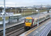 The 11.57 service to Helensburgh Central (11.21 ex-Edinburgh Waverley) pulls into platform 2 at Blackridge on 13 January 2011. Note the old formation running across the centre of the photograph, which once carried a mineral line from Woodend Junction (located just out of shot in the right background) serving Blackrigg No 2 Colliery. [See image 32303]  <br> <br><br>[John Furnevel /01/2011]