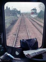 A view from an eastbound DMU approaching Inchture Level Crossing in January 1989. The box was subsequently demolished. The driver's newspaper provides an alterative destination blind!<br><br>[Ewan Crawford&nbsp;25/01/1989]