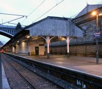 A pre-dawn look along the former 'Sub' Platforms 8 and 9 on 15 <br> January 2011.� The awning is looking a bit tired; it is destined to be replaced in the Waverley station improvement programme, though the Victorian ironwork will be retained.� Waverley is one of only 7 stations outside London owned by Network Rail (as is Glasgow Central) and so has NR signage.� Waverley's symbol is a castellated letter E, but it's bell shape makes it look rather like a pound sign.� I'm sure this wasn't the intention, though I like a '�' as much as the next miser.<br> <br><br>[David Panton&nbsp;15/01/2011]