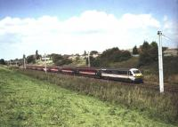 A Virgin West Coast service, comprised of mixed liveried stock, heads south on the WCML at Farington Curve Junction in September 1999. The DVT at the front and class 87 on the rear are still in <I>InterCity</I> livery while the entire rake of coaches has been rebranded in Virgin colours.<br> <br><br>[John McIntyre&nbsp;/09/1999]