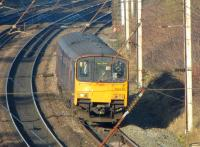 Looking through the OHLE as 150134 heads south of Skew Bridge <br> towards Farington Curve Junction with a Preston to Hazel Grove service on 21 January 2011.<br> <br><br>[John McIntyre&nbsp;21/01/2011]