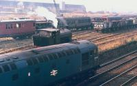 D5302 passes Niddrie West Yard, Edinburgh, watched by the crew of NCB Lothians Area no 25 (Barclay 2358 of 1954) in the exchange sidings for Niddrie Landsale Yard in 1971.� Beyond are vehicles belonging to the civil engineer who had taken over the sidings by this time.<br><br>[Bill Roberton&nbsp;//1971]