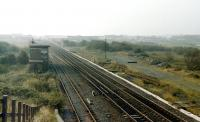 View north west at Stevenston no 1 signal box in 1985. The trackbed of the LMS connection to the Caledonian line to Montgomerie Pier is on the right with the abutment of the Caley bridge in the background.<br><br>[Colin Miller&nbsp;//1985]