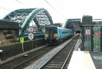 A Carlisle - Middlesbrough train crossing the River Wear after passing through the platforms of St Peters station, Monkwearmouth, in July 2004. The station was built as part of the Tyne & Wear Metro development. The former Monkwearmouth station, now a museum, stands 100m behind the camera [see image 17890].<br><br>[John Furnevel&nbsp;10/07/2004]