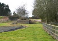 The remains of the station at Leadburn on the Peebles Railway, one time junction for the Dolphinton line. The station closed in 1955 and, following complete closure of the Peebles line in 1962, was turned into a picnic site [see image 50015]. Nowadays the site is inaccessible, secured by a padlocked gate alongside the A6094, from which this photograph was taken on 8 March 2015 looking south west towards the junction.<br><br>[John Furnevel&nbsp;08/03/2015]