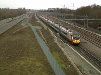 Road vs. rail: a down Pendolino forms an orderly queue for platform 6 at Milton Keynes as road traffic (more vehicles, less passengers) passes on the A5. View looks North on 4 February.<br><br>[Ken Strachan&nbsp;04/02/2011]