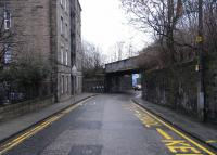 The Abbeyhill Loop and direct connection between Waverley and Leith <br> left the ECML (to the right in this picture) at Abbeyhill Junction and crossed the street called just Abbeyhill before entering Abbeyhill station.� Although the line has been lifted for years the bridge over Abbeyhill survives, and is seen here on 12 February looking east.� The ECML itself crosses Abbeyhill a bit further on, reducing the advantage in removing this overbridge which is perhaps why it's still there. The Junction was overlooked by the top storeys of Brand Place, a single tenement with an address of it's own, which it retains.<br><br>[David Panton 12/02/2011]