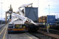A lorry-mounted crane transfers containerised timber from road to rail at Coatbridge Freightliner terminal, as part of a 2001 demonstrator project managed by the photographer for Scottish Enterprise.<br> <br><br>[David Spaven //2001]