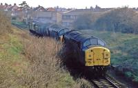 A train of Class 37s is seen shortly after passing through the former Felixstowe Beach station running towards the junction near Felixstowe. From there, the locomotives will head to Ipswich for servicing [see image 34707]. At the time, in April 1984, the heavy freightliner trains to the container port at Felixstowe were double-headed and this peculiar working helped ease the congestion on the line before the loop to Trimley was built.<br><br>[Mark Dufton&nbsp;14/04/1984]