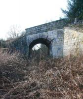 Looking south west towards the site of Roslin station (now a housing development) along the overgrown EL&RR trackbed on 28 February 2011. The rail route and public walkway from Loanhead have parted company by this time with the latter now crossing the heavily overgrown formation via the skew-arch overbridge and continuing towards the centre of the village just over quarter of a mile away to the left.<br> <br><br>[John Furnevel&nbsp;28/02/2011]