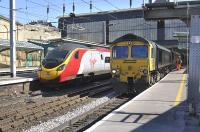 Freightliner Heavy Haul 66551 pauses at Carlisle platform 3 for a crew change on 18 March with the 4S70 Drax PS - Ayr empties, as a Euston-bound Pendolino arrives at platform 4.<br><br>[Bill Roberton&nbsp;18/03/2011]