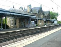 View south at Morpeth station on the ECML on a May afternoon in 2004. Visible just beyond the attractive station buildings on the up platform is the start of the infamous <I>Morpeth Curve</I>, the most severe curve (17 chains (340 m) radius) on any main line in Britain, turning through almost 90 degrees immediately south of the Station. The curve has been the scene of three major derailments over the years. There is a permanent speed restriction of 50mph through this section of the ECML.<br><br>[John Furnevel&nbsp;28/05/2004]